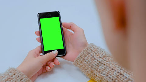 Woman looking at black smartphone device with empty green screen Footage