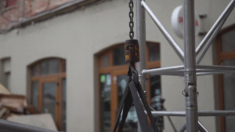 View of small crane hook with chain connected to grey aluminium structure Footage