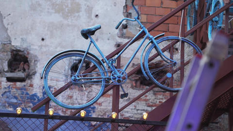 Vintage bike covered by blue paint is hanged on brown handhold nearby brick wall Footage