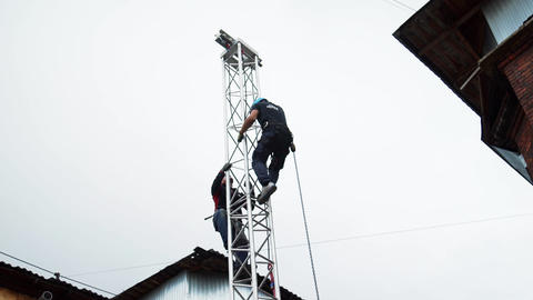 Two guys workers in construction safety uniform and helmet climb up on PA tower Footage