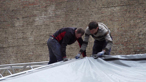 Two mature men are mounting grey dome to metallic grey stage substructure Live Action
