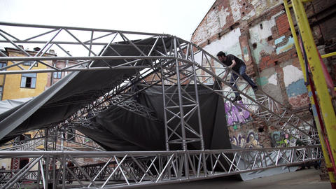 Guy in t-shirt and glasses covers big stage structure by grey tarpaulin dome Footage