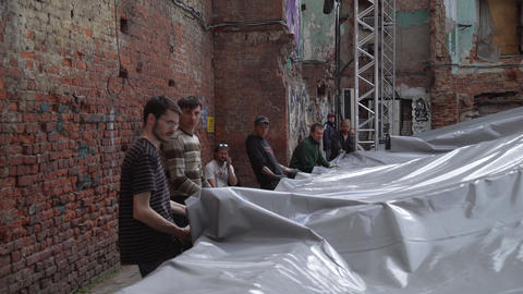 Young men are covering aluminium stage structure with grey opaque tarpaulin Footage