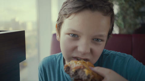 Footage happy young teenager eating tasty burger in fast food restaurant Footage