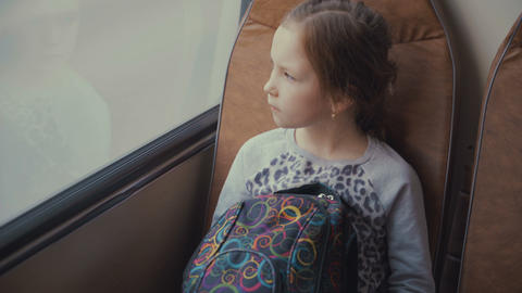 Young, beautiful girl passenger with school bag in the moving school bus looking Footage