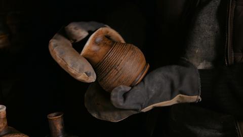 Potter examining ceramic pot GIF