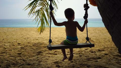 boy of two years swings on a swing on the beach near the ocean Footage