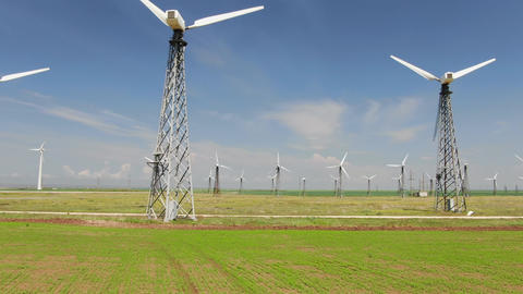 Row of towers with wind turbines in blue sky background GIF