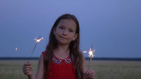 Portrait of a girl with sparklers in their hands at evening Footage