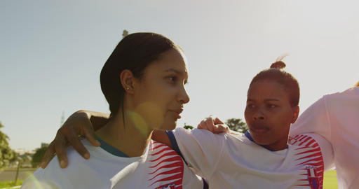 Female soccer player encouraging her team while standing arm to arm on soccer field. 4k Live Action