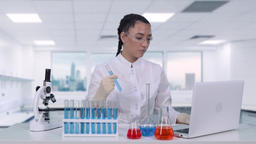 Female researcher examines a liquid in a test tube A female scientist conducts Footage