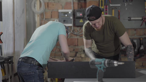 Two guys working in a small workshop with tools. Two woodworkers craft wood Live Action