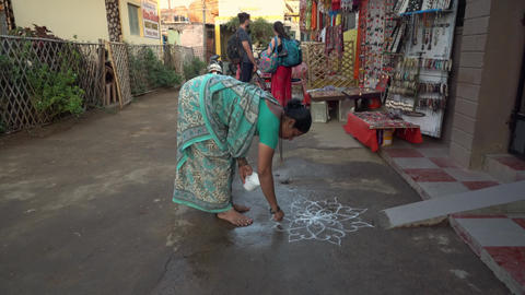 A woman draws a prayer drawing on the ground Live Action