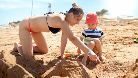 Photo of mother with little son building sand castle on the sea beach. People Photo