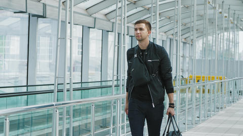 A young confident man with a handbag in modern airport terminal Footage