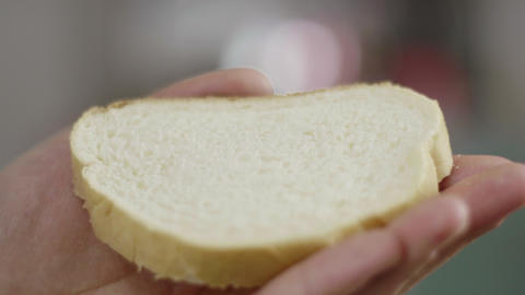 Closeup of male hands spreading butter on bread in kitchen in slow motion Footage