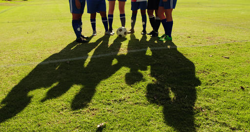 Female soccer team standing arm to arm on soccer field. 4k Live Action