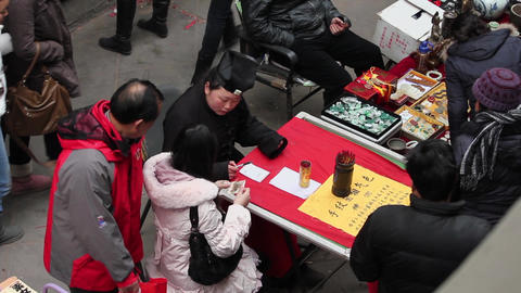 XI'AN CHINA - FEB 06 2012: Fortuneteller tell fortunes for a girl in market Live Action