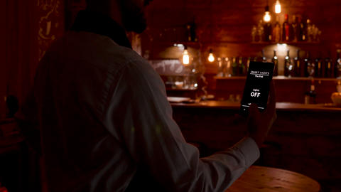 Waiter gives a voice command to the smartphone to turn on the lights Footage