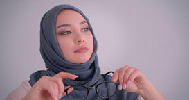 Close-up portrait of muslim businesswoman in hijab plays with her eyeglasses Archivo