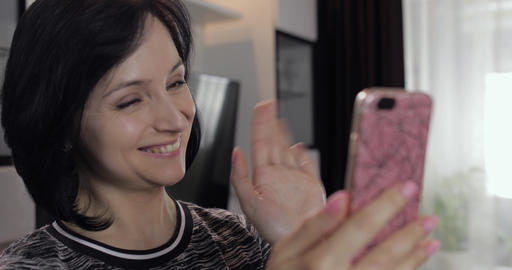 Woman having video chat using smartphone enjoying chatting to friend Footage