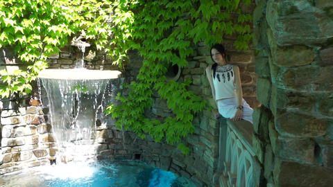 A young girl in a white dress sits near a fountain and stone walls with foliage in the background GIF