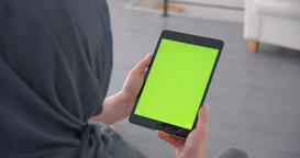 Muslim businesswoman in hijab watches attentively at tablet with green chroma Footage