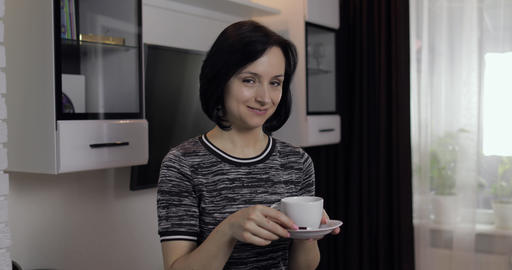 Portrait of young brunette woman eating chocolate and drinking coffee from cup Footage