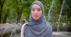 Portrait of pretty muslim student in hijab smiling modestly into camera standing Archivo