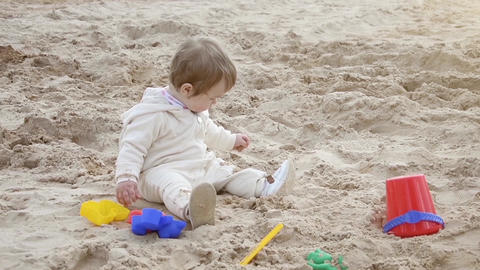 [alt video] Girl on the beach playing in the sand with toys