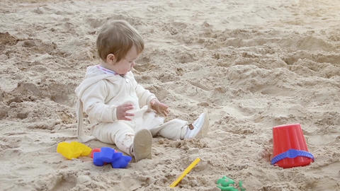 Girl on the beach playing in the sand with toys Archivo