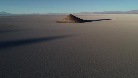 Aerial drone scene of general view of natural isolated pyamid in wide brown and white salar at Footage