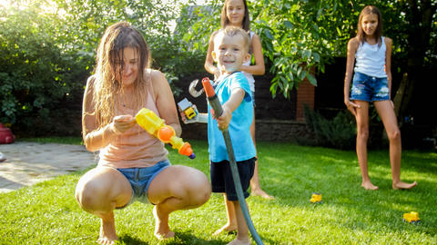 Adorable 3 years old toddler boy splashing water from plastic toy gun at house Photo