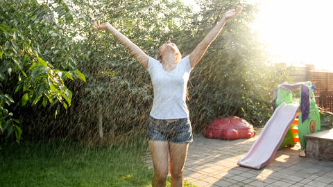 Portrait of happy laughing young woman with long hair in wet clothes dancing Photo
