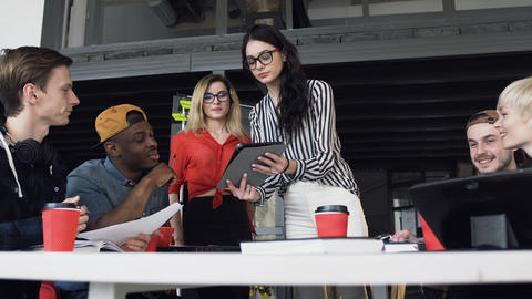 Young businesswoman presenting new business plan to here young hipster team Live Action