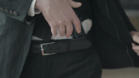 Unrecognizable man in a suit pushes the jacket back and shows the gun hidden Live Action