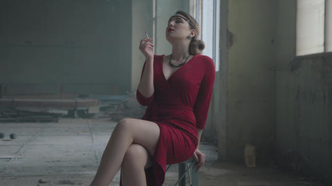 Elegant woman in red elegant dress sitting on the chair in the abandoned Footage