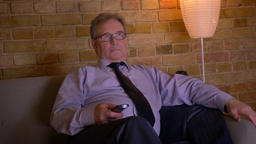 Portrait of senior businessman in costume relaxing in front of TV after hard Archivo