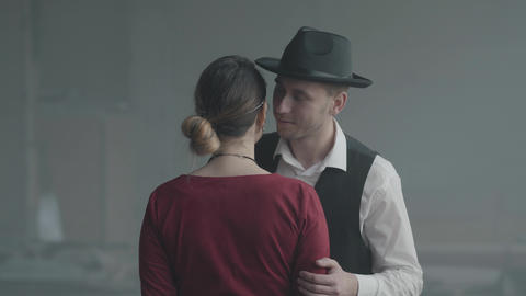 Handsome confident man in a hat whispering joke on the ear of elegant lady who Footage