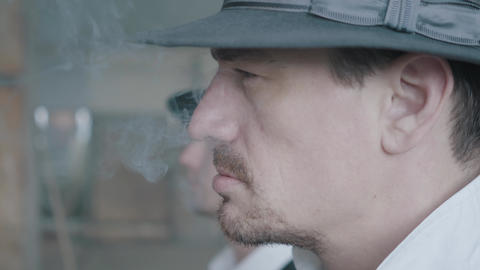[alt video] Two men in fedora hat stand serious and scary smoking a...