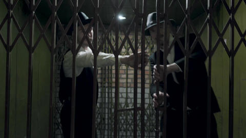 Two gangsters men in formal suits and fedora hat opening a metal forged gates Archivo