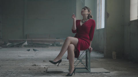 Portrait elegant woman in red elegant dress sitting on the chair in the Footage
