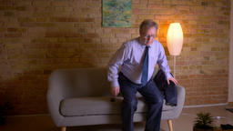 Portrait of senior businessman in costume sits down on sofa and switches on the Archivo