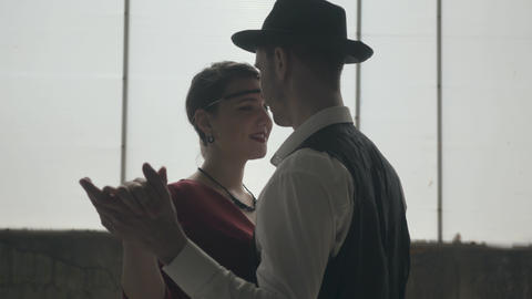 Man in fedora hat, classical suits and woman in style cloth dancing in dirty Footage