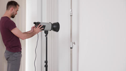 Professional fashion photographer rises the flash lights and powers it up Live Action