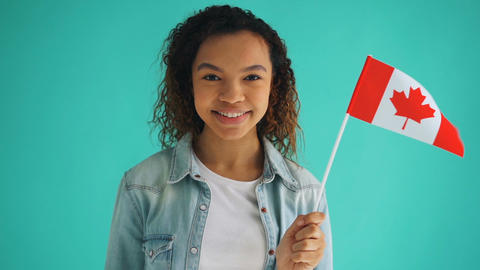 Slow motion of Canadian citizen mixed race girl holding national flag smiling Footage