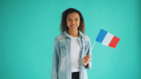 Slow motion of mixed race French lady waving official flag and smiling Footage