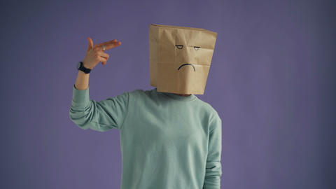 Girl with paper bag on head making gun gesture shooting committing suicide Live Action