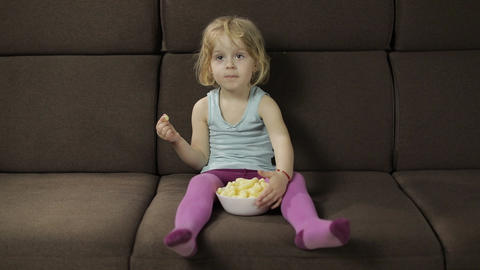 Girl sitting on sofa and eating corn puffs. Child watching tv, taste puffcorns Archivo