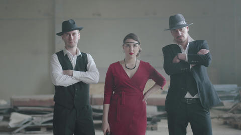 Portrait two confident well-dressed men standing in two sides of a woman in red Footage
